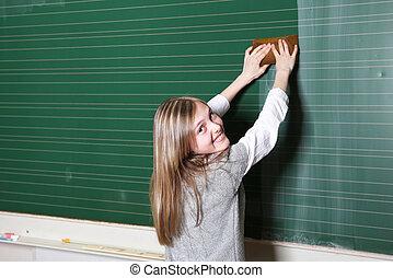 Smiling girl cleaning school blackboard