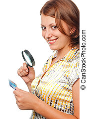 Smiling girl considers a credit card through a magnifier