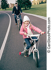 Smiling girl cycling with father