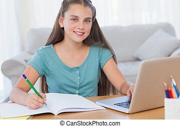 Smiling girl doing her homework