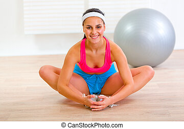 Smiling girl doing stretching exercises at home