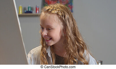 Smiling girl draws a picture in the studio