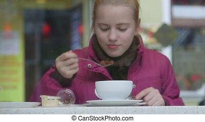 Smiling girl eating dessert at coffee shop as seen through...