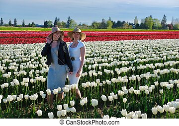 Smiling girl friends in colorful tulips field.