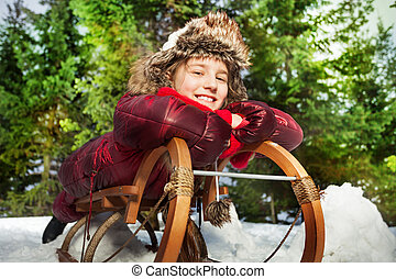 Smiling girl having fun in winter snow on a sledge