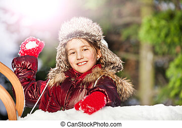 Smiling girl having fun with snowball fight