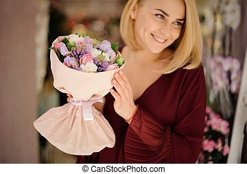 Smiling girl holding a beautiful and colorful bouquet