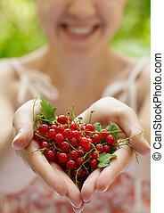 Smiling girl holding a handful of red currants