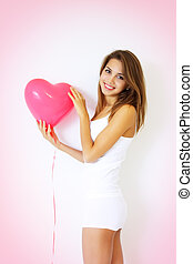 smiling girl holding a large decorative heart