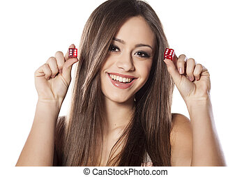 smiling girl holding a pair of dice for gambling with a winning combination