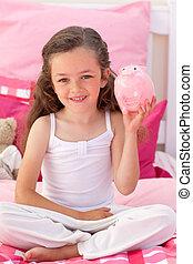 Smiling girl holding a piggybank