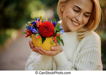Smiling girl holding a pumpkin decorated with red and blue flowers
