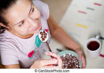smiling girl holding a spoon with chocolate balls and milk near the mouth over the table