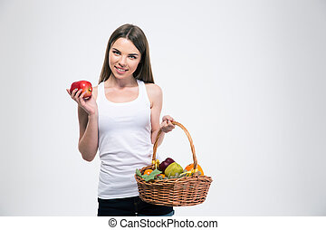 Smiling girl holding basket with fruits