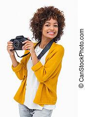 Smiling girl holding digital camera