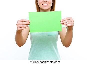 Smiling girl holding green sheet of paper