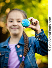 smiling girl holding little Earth at hand