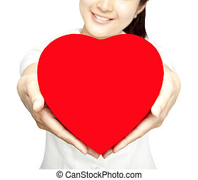 Smiling girl holding red heart symbol