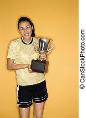 Smiling girl holding trophy.