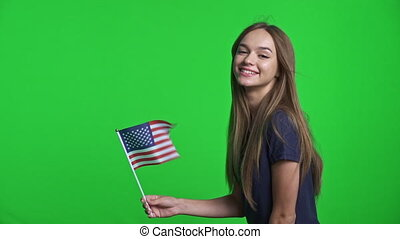 Smiling girl holding USA flag fluttering on wind and gesturing thumb up at the end, over green chroma key background