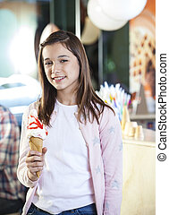 Smiling Girl Holding Vanilla Ice Cream At Parlor