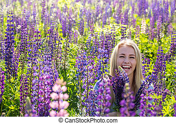 Smiling girl in a field of lupines