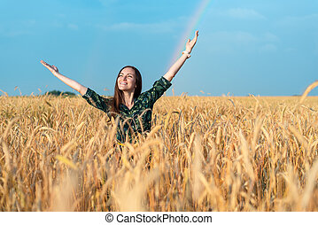 Smiling girl in a field with wheat looking at the sky hands pulling up, freedom concept