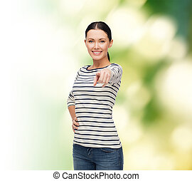 smiling girl in casual clother pointing at you