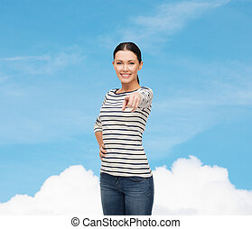 smiling girl in casual clothes pointing at you