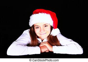 smiling girl in christmas hat over dark
