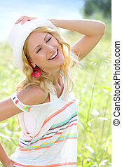 Smiling girl in countryside wearing hat