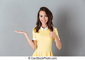 Smiling girl in dress holding copy space on a palm