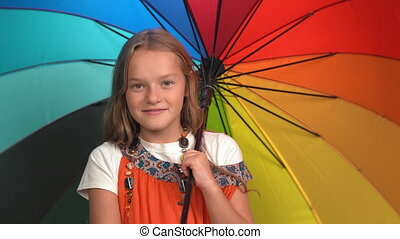 Smiling girl in mother's sundress with beads twists open bright multi-colored umbrella. Caucasian child looks at camera and smiles. Black background. High quality 4k footage