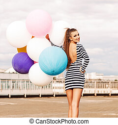 smiling girl in open-back black and white striped short dress and white high top sneakers with bunch of multicolored balloons turns back