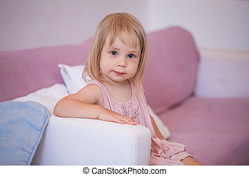 Smiling girl in pink dress at home