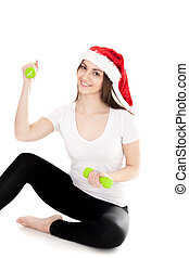 Smiling girl in red Santa Claus hat holds green colored dumbbell