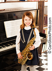Smiling girl in school uniform with alto saxophone - Smiling...