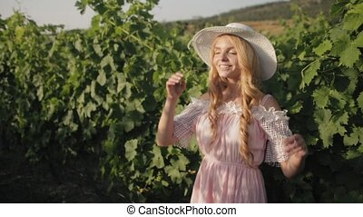 Smiling girl in the beautiful dress and hat standing next to the grapevine
