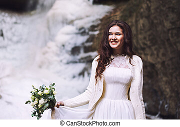 Smiling girl in wedding dress with bouquet in front of glacier