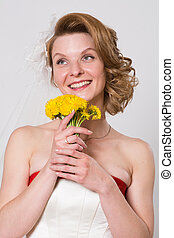 Smiling girl in wedding dress with flowers
