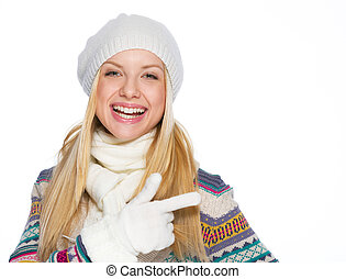 Smiling girl in winter clothes pointing on copy space
