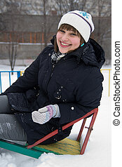Smiling girl in winter - Smiling young girl sitting on a...