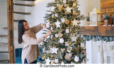 Smiling girl is decorating Christmas tree with balls and lights enjoying holidays and creative activity. Beautiful decorated room with fireplace is visible.