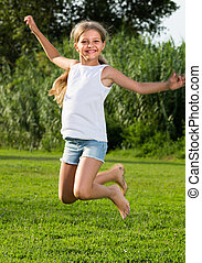 smiling girl jumping on grass