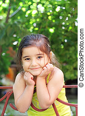 Smiling girl leaning on fence