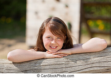 girl leaning on tree trunk at playground