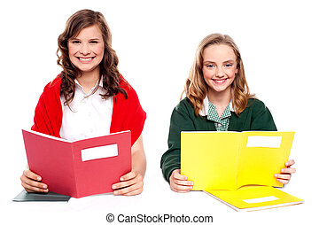 Smiling girl learning from school books