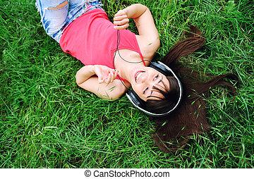 Smiling girl listening music .