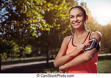 Smiling girl listening to music before training