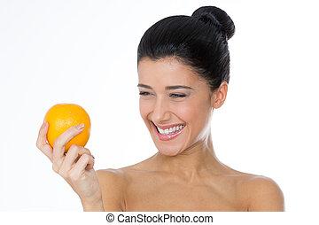 smiling girl looking at an orange